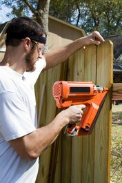 Picture of a man in a white shirt using a nail gun to put up a wood fence