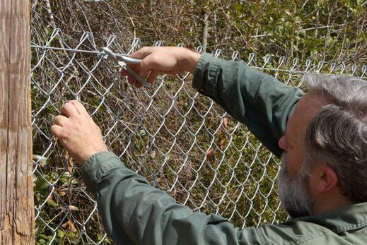 Picture of a man in a green shirt installing a chain link fence