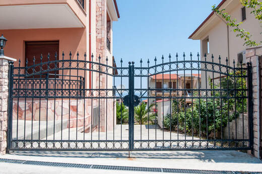 Picture of a wrought iron security gate next to a pink house