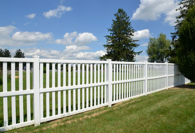 Picture of a white vinyl fence separating two properties
